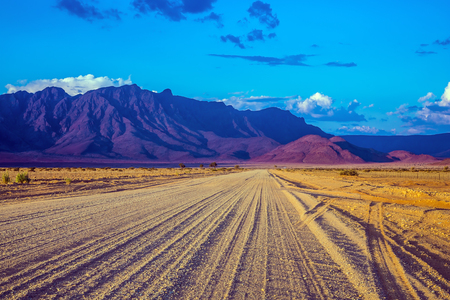 ecotourism: The dirt road in Namib-Naukluft national park goes to distant mountains. Travel to Namibia. Ecotourism in Africa