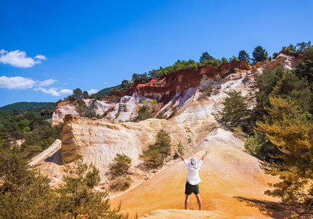 admires: Elderly man admires a magnificent landscape. Orange and red picturesque hills in Roussillon Stock Photo