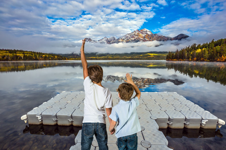 motor boats: Two boys stand on the plastic dock for motor boats. Cumulus clouds over the Pyramid mountain and Pyramid Lake