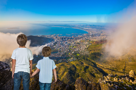 table mountain national park: The concept of active tourism and recreation. Travel to Africa. Two boys standing on top of Table Mountain in the clouds Stock Photo