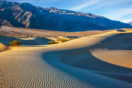 stovepipe hat: Small sandy ripples on orange barkhans. Mesquite Flat Sand Dunes in California. Woman in straw hat  photographing sand waves
