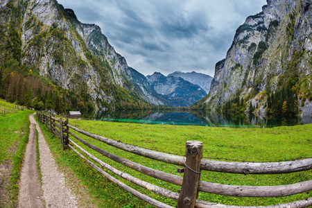 ecological tourism: The Bavarian Alps. The magic blue lake Obersee and the fenced footpath to it. Concept of active tourism and ecological tourism