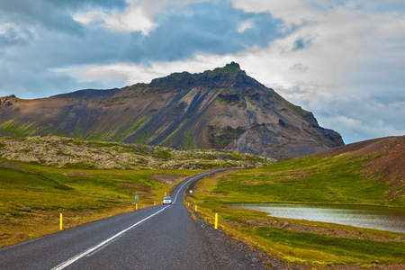 Cloud Iceland in the summer. The road passes through the picturesque landscape in the mountains and lakes