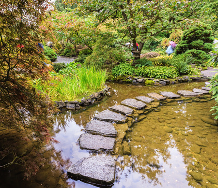 The track of the stones in the Japanese part of the garden. Amazingly beautiful decorative private garden in western Canada Butchart Gardens Stock Photo