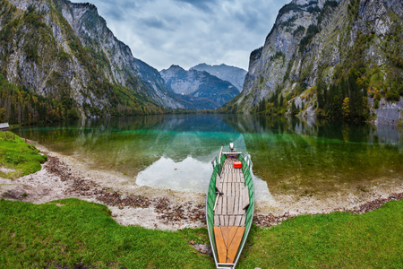 ecological tourism: The magic blue lake Obersee in Bavarian Alps. Fishing boat with a small engine in shallows of the lake. Concept of active tourism and ecological tourism