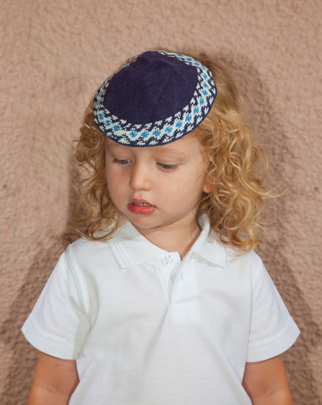 kippah: Adorable Jewish child in a blue skullcap. Little boy with long blond curls and blue eyes