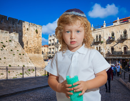kippah: Little boy with long blond curls and blue eyes. Adorable Jewish child in a blue yarmulke. Jerusalem, the city of King David