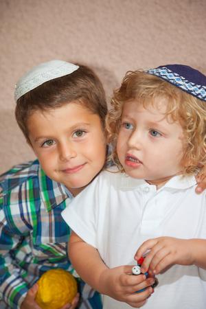 kippah: Two beautiful Jewish boy in skull-caps. The elder brother holds a ritual fruit - Etrog. Sukkot