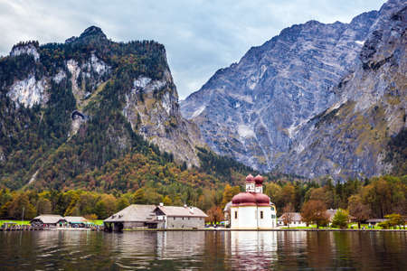 dreamlike: Dreamlike beauty of on the lake Konigssee. Red domes and white walls of the Church of St. Bartholomew  reflected in the water