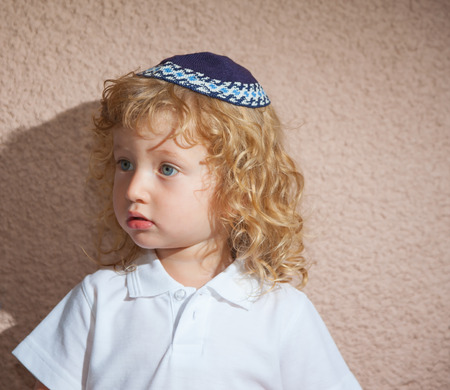 kippah: Little boy with long blond curls and blue eyes. Adorable Jewish child in a blue yarmulke - skullcap Stock Photo