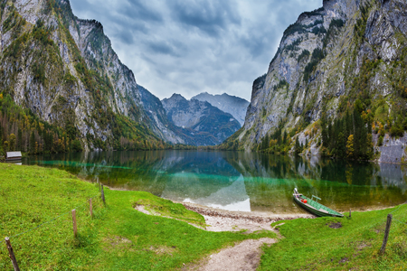 ecological tourism: Fishing boats with a small engine in shallows of the lake. The magic blue lake Obersee in Bavarian Alps. Concept of active tourism and ecological tourism