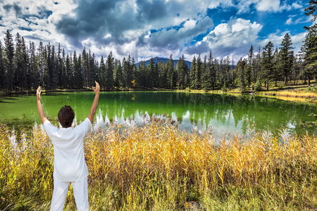 Middle-aged woman, dressed for yoga, Sun Salutation on the shore of small lake. Jasper National Park in the Rocky Mountains of Canada. Patricia Lake