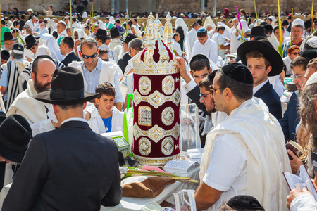talmud: JERUSALEM, ISRAEL - OCTOBER 12, 2014: The area in front of Western Wall of Temple filled with people.  The Jews brought the Torah scroll for prayer Editorial