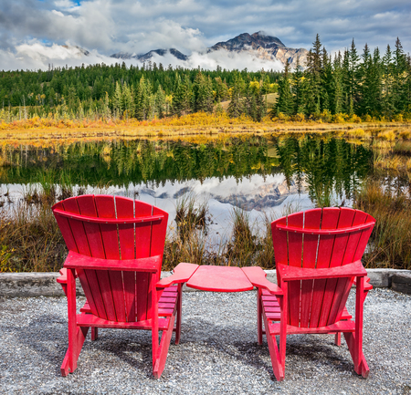 interconnected: Jasper National Park in the Rocky Mountains. Two red plastic chairs, interconnected, are on the lake. On shores of the lake grow coniferous forests