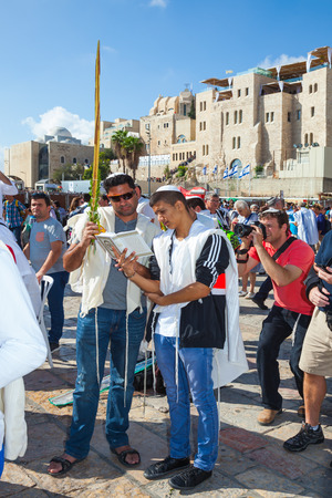 talmud: JERUSALEM, ISRAEL - OCTOBER 12, 2014:  The area in front of Western Wall of Temple filled with people.  The Jews of tallit hold four ritual plants. Morning autumn Sukkot, Blessing of the Kohanim