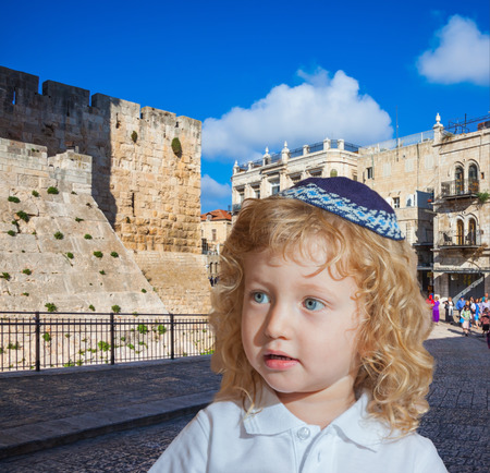 kippah: Adorable Jewish child in a blue yarmulke. Little boy with long blond curls and blue eyes. Jerusalem, the city of King David