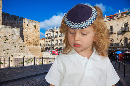 kippah: Jerusalem, the city of King David. Little boy with long blond curls and blue eyes. Adorable Jewish child in a blue skullcap
