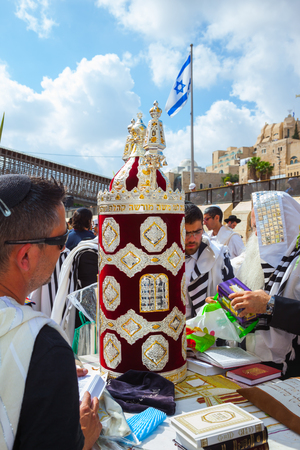 JERUSALEM, ISRAEL - OCTOBER 12, 2014: Sukkot. The area in front of Western Wall of Temple filled with people. Imposition of a Sefer Torah for prayer. The Jews of ritual tallit worship with prayer books
