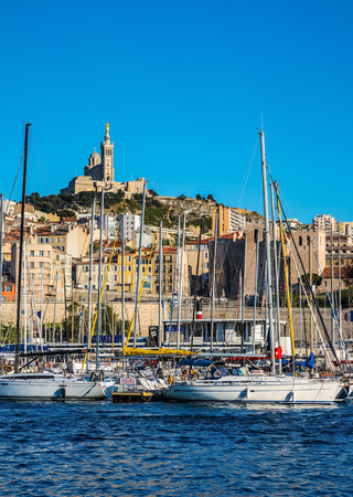 Marseilles. The water area of the Old Port - yachts, speedboats and fishing boats. On the hill - splendid Basilica of Notre-Dame de la Garde