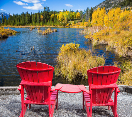 ecological tourism: Two comfortable red deck chairs on the lake. Concept of ecological tourism. Indian summer in the Rocky Mountains of Canada
