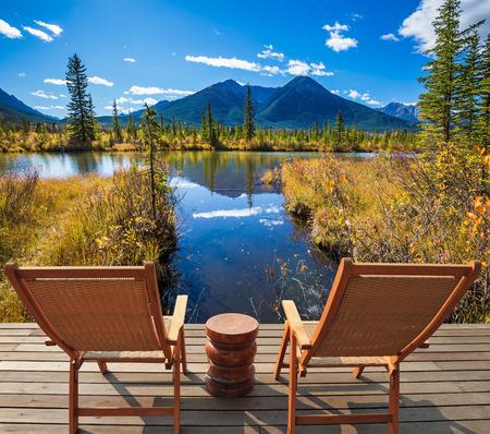 turismo ecologico: Dos cómodas sillas de madera y una pequeña mesa redonda en el lago. Concepto de turismo ecológico. verano indio en las Montañas Rocosas de Canadá
