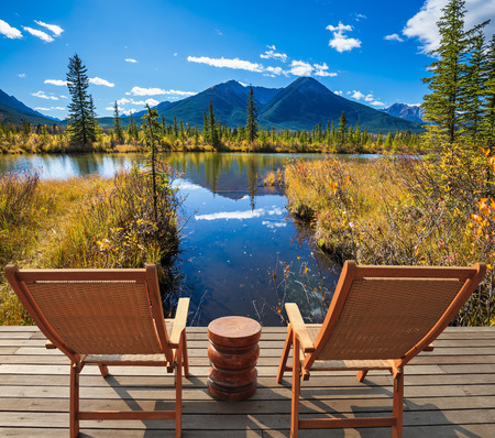 ecological tourism: Two comfortable wooden chairs and a small round table on the lake. Concept of ecological tourism. Indian summer in the Rocky Mountains of Canada