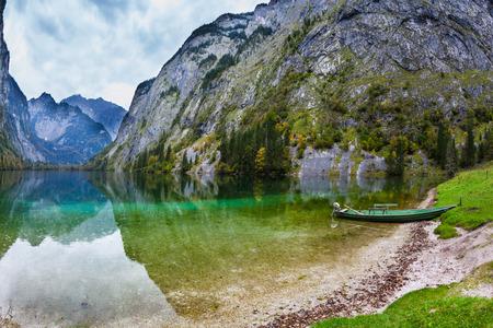 turismo ecologico: Barco de pesca con un pequeño motor en aguas poco profundas del lago. El lago azul mágica Obersee en los Alpes bávaros. Concepto de turismo activo y turismo ecológico Foto de archivo