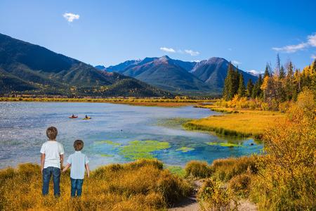 turismo ecologico: Dos niños pequeños de la mano sobre el lago. Concepto de turismo ecológico. verano indio en las Montañas Rocosas de Canadá