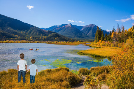 ecological tourism: Two little boys holding hands on the lake. Concept of ecological tourism. Indian summer in the Rocky Mountains of Canada