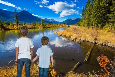 turismo ecologico: Dos niños pequeños de la mano sobre el lago. verano indio en las Montañas Rocosas de Canadá. Concepto de turismo ecológico Foto de archivo