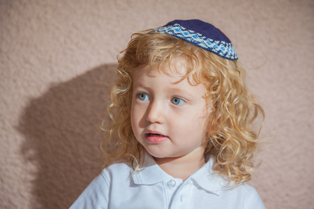kippah: Adorable Jewish child in a blue yarmulke - skullcap. Little boy with long blond curls and blue eyes Stock Photo