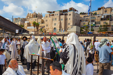 talmud: JERUSALEM, ISRAEL - OCTOBER 12, 2014:  The area in front of Western Wall of Temple filled with people.  Morning autumn Sukkot, Blessing of the Kohanim. The Jews of tallit hold four ritual plants Editorial