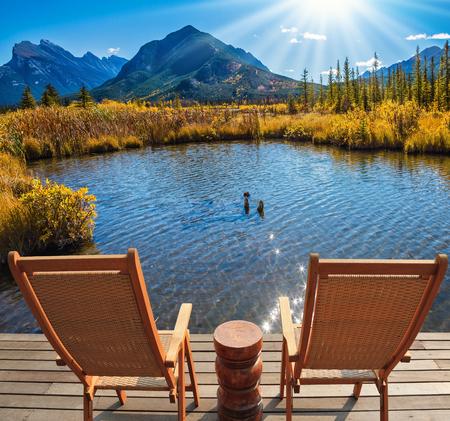 turismo ecologico: Dos cómodas sillas de madera y una pequeña mesa redonda en el lago. verano indio en las Montañas Rocosas de Canadá. Concepto de turismo ecológico Foto de archivo