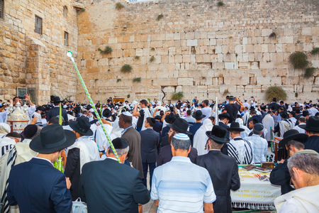 talmud: JERUSALEM, ISRAEL - OCTOBER 12, 2014:  The area in front of Western Wall of Temple filled with people. The Jews of ritual clothes - tallit hold four ritual plants. Morning autumn Sukkot, Blessing of the Kohanim