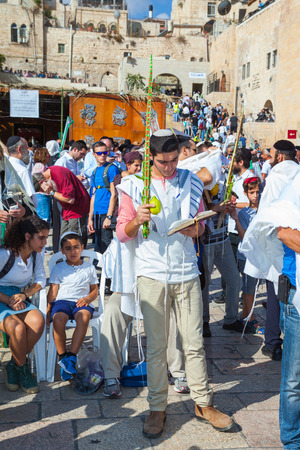 talmud: JERUSALEM, ISRAEL - OCTOBER 12, 2014: Jews wearing tallit hold ritual plants. Sukkot, Blessing of the Kohanim. The area in front of Western Wall of Temple filled with people