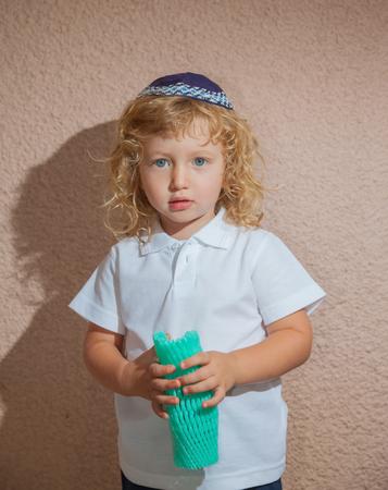 kippah: Adorable Jewish child in a blue  skullcap - yarmulke. Little boy with long blond curls and blue eyes