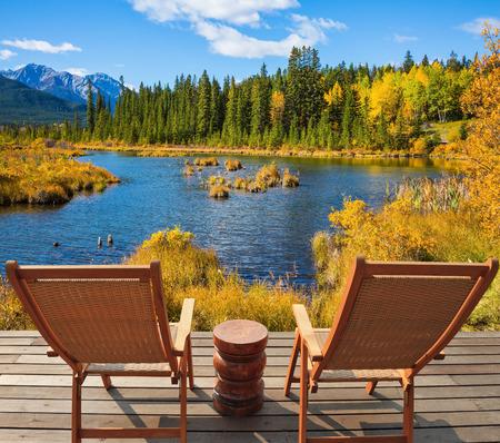 turismo ecologico: Dos cómodas tumbonas de madera en la orilla del lago. Concepto de turismo ecológico. verano indio en las Montañas Rocosas de Canadá