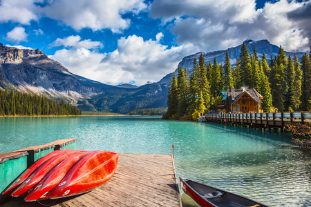 activ: Brilliant red kayaks dry upside down. Emerald Lake in Canadian Rockies. Concept of active vacation and tourism Stock Photo