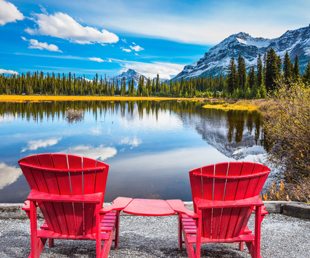 The beautiful nature in northern Rocky Mountains of Canada. Two red comfortable deck chairs on the lake Stock Photo