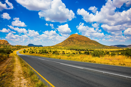 The good asphalt highway in Namibia. Fluffy clouds over the savannah. Along the road low trees and yellowed grass Stock Photo