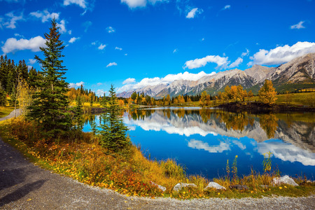 canmore: The concept of hiking. Path around the lake. Canmore, near Banff National Park. Mountains and scenic cumulus clouds are reflected in the water