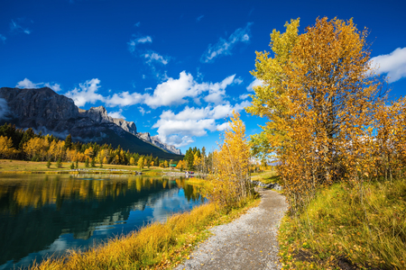 canmore: Canmore, near Banff Park. Path around the lake. The concept of hiking. Majestic mountains and autumn aspens reflected in the water Stock Photo