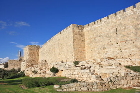 Defensive wall of the ancient holy Jerusalem, lit by the bright sun. Wonderful green lawn