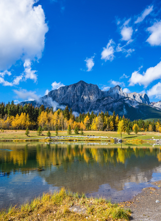 canmore: Canmore, near Banff National Park. The concept of recreational tourism. Majestic mountains and scenic cumulus clouds are reflected in the water