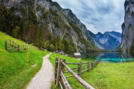 turismo ecologico: Concepto de turismo activo y el turismo ecológico. Los Alpes bávaros. El lago azul mágica Obersee y el sendero vallado a ella Foto de archivo