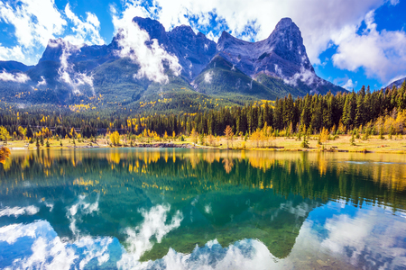canmore: Magnificent mountains Three Sisters  and scenic cumulus clouds are reflected in the water. Rocky Mountains, Canmore. The concept of recreational tourism