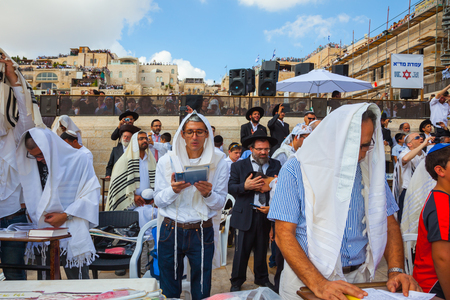 talmud: JERUSALEM, ISRAEL - OCTOBER 12, 2014:   Morning autumn Sukkot. The area in front of Western Wall of Temple filled with people. The Jews of ritual tallit are holding prayer Editorial