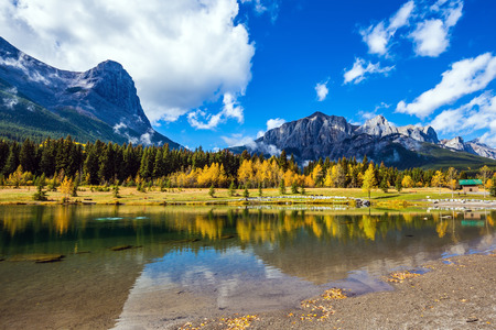 canmore: Majestic mountains and scenic cumulus clouds are reflected in the water. Canmore, near Banff National Park. The concept of recreational tourism Stock Photo
