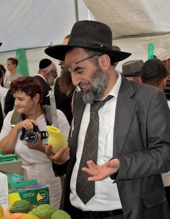 chooses: JERUSALEM, ISRAEL - SEPTEMBER 18, 2013: Religious Jew chooses carefully ritual fruit - etrog for Sukkot. In the background - woman - photographer
