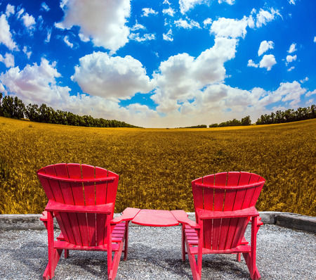 ecotourism: Convenient, comfortable red chairs in a wheat field. The concept of eco-tourism. Rustic vacation